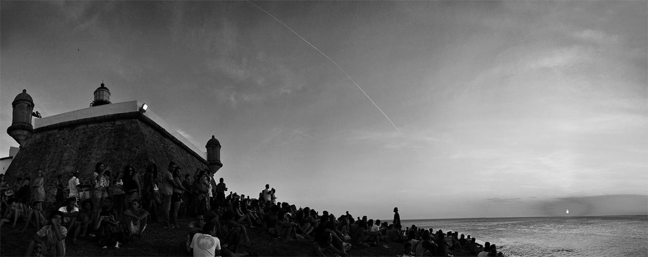 Multidão assiste o pôr do sol no farol da barra